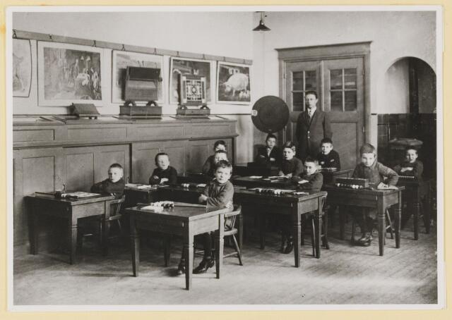 """080637 - """"Huize Assisië"""". Schoollokaal. Achter in het lokaal de kachel."""