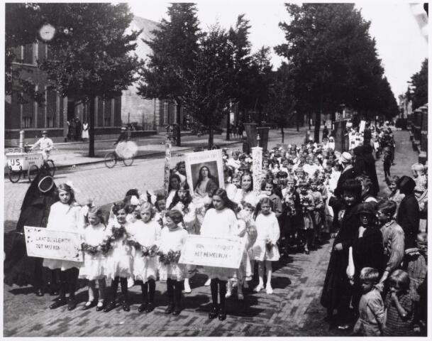 012027 - H. kindsheid optocht in de Goirkestraat in de jaren twintig. Links de bakfiets van H.C. Staps ijscohandelaar Atelierstraat 80.
