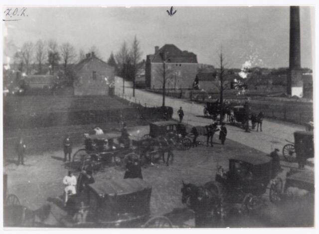 039574 - Op de achtergrond het terrein van de voormalige steenfabriek van de firma Claesen aan de Hoefstraat. De schoorsteen werd circa 1923 afgebroken. Op de achtergrond het huis van de familie A. Claesen-Schoenmakers, gebouwd in 1920 door architect Jan van der Valk. De koetsen op de voorgrond staan voor de kerk van de Hoefstraat.