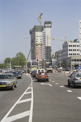 TLB023000873_001 - Zicht vanaf de Spoorlaan op het in aanbouw zijnde Interpolis gebouw, met rechts op de voorgrond het kantoor van de ABN-AMRO en de BVG op de hoek met de Heuvelring.