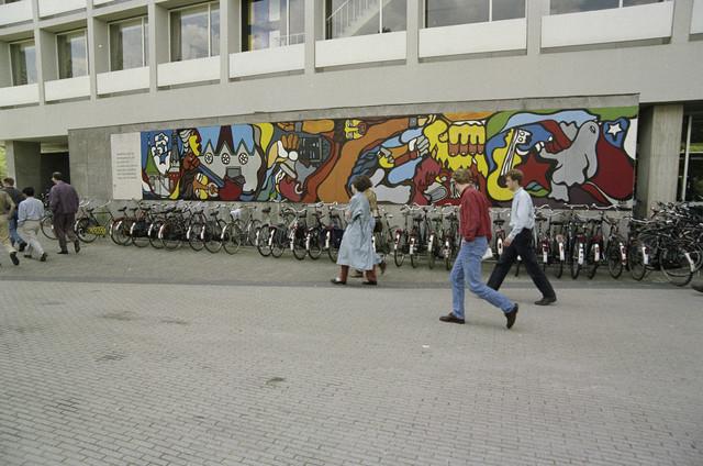 """TLB023000335_001 - Muurschildering op de gevel van het Tjalling C. Koopmansgebouw van de universiteit (KUB / UvT) ter herdenking van de staatsgreep in Chili op 11 september 1973 en tevens een protest tegen de schending van mensenrechten waar ook ter wereld"""". De Chileense Schilderbrigade """"Brigada Ramona Parra"""" heeft ook in Nederland veel muurschilderingen gemaakt o.a. deze naar ontwerp van Jorge Kata Nunez."""