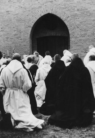 105212 - Monniken geknield (op de rug gezien)voor de ingang van de kerk. Kerkwijding van de nieuwe kloosterkerk van de Sint Paulus Abdij in Oosterhout, gebouwd tussen 1953 en 1956 onder architectuur van J. Sluymer uit Enschede. Kloosters