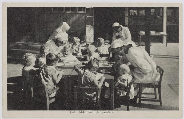 046355 - Medisch kinderdagverblijf Kleuterheil. Verplegend personeel met kleuters aan het middagmaal.