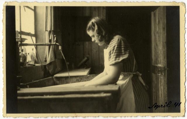 650373 - Schmidlin. Johanna Maria Gerarda (Annie) Schmidlin aan de speolbak van het fotoatelier te Dongen. Annie was 'fotografiste' van beroep en emigreerde in 1946 met haar ouders naar Zwitserland. Dongen, 1941.