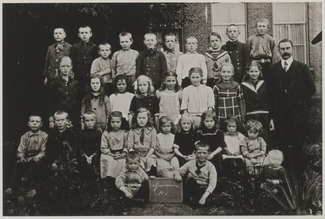 058719 - Basisonderwijs. Klassenfoto.  Openbare school in 's Gravenmoer in 1914.  Rechts Jan Pruijsen (leraar tussen 1912 en 1920). Op de bovenste rij staat Martinus Beunis Rutters (geboren 22 maart 1906) als vierde van links.