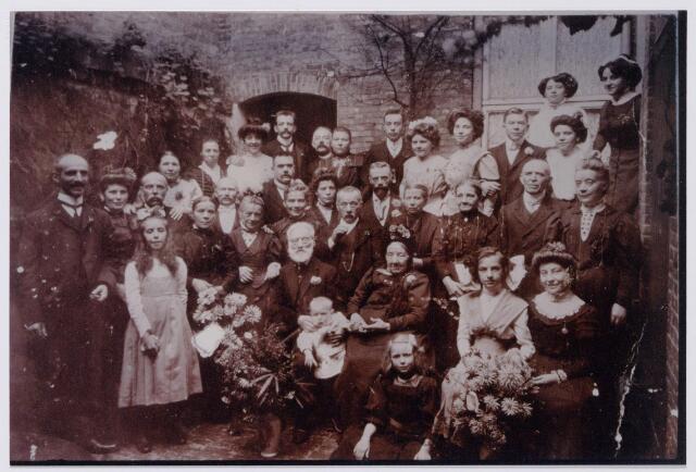 043809 - Diamanten bruiloft van Josephus Niesten en Lesia van Osta te Tilburg. Hij werd geboren te Ommerschans op 29 juli 1829 en was kleermaker van beroep. Zij werd geboren te Ommerschans op 9 mei 1828. Het echtpaar trouwde te Avereest op 20 oktober 1849. Op de foto meisje op de voorgrond Maria Kamerbeek, pleegdochter van het echtpaar Niesten-de Groot, later non geworden, en tussen het diamanten echtpaar kleinkind C.W.M. Peters. Zittend van links naar rechts: het diamanten paar, kleindochter Van Berkel uit de U.S.A. en kleindochter Anna Niesten, dochter van het echtpaar Niesten-Mijland. Op de volgende rij v.l.n.r. Adrianus van Velthoven, zijn vrouw Gon Luijben, rechts voor haar kleindochter Van Berkel U.S.A., achter haar Frans Beekmans, schoenmaker, geboren te Helvoirt op 22 maart 1857, rechts voor hem zijn vrouw Adriana Maria (Marie) Beekmans-Niesten, geboren te Avereest op 8 april 1859,  rechts boven haar Jan van Diessen, smid te Tilburg, geboren te Heusden op 1 november 1858, rechts voor hem zijn vrouw Adriana Maria Johanna (Jo) van Diessen-Niesten, geboren te Dedemsvaart op 7 september 1850,  vervolgens Johanna Lucia van Berkel-Niesten U.S.A., geboren te Avereest op 1 november 1861, rechts achter haar Maria Johanna Josephina (Fien) Peters-Niesten, geboren te Helmond op 1 mei 1872,  rechts voor haarJosephus Lambertus Augustinus ( Bert) Niesten, kleermaker te Gerwen, geboren te Avereest op 8 september 1856, rechts achter hem Josephus Marinus Niesten, bakker, geboren te Avereest op 25 februari 1866 (hij trouwde Ida Sauren en woonde in Boxtel)  vervolgens Francina (Sien) Niesten-de Groot (vrouw van Bert Niesten), geboren te Nuenen op 23 september 1852,  Maria Catharina Luijben-Niesten, geboren te Avereest op 16 maart 1854,  Caspar Leonardus (Caspar) Luijben, kleermaker te Helmond geboren aldaar op 24 september 1845,  en Lucia Johanna Maria (Luus) Niesten. geboren te Helmond op 13 mei 1870, ongehuwd winkeljuffrouw te Rotterdam.  Bovenste rij v.l.n.r.: twee dames Van