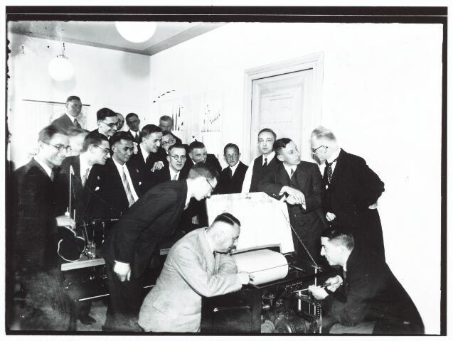 051948 - Hoger Voortgezet Onderwijs. R.K. Handelshogeschool te Tilburg. Eerste Tilburgse Hogeschooldag. Heden werd de eerste Tilburgse Hogeschooldag gehouden. Men weet dat op instignatie van Prof. dr. Martinus J.H. Cobbenhagen is opgericht de Tilburgse Academische Ecomische Kring, Kortweg T.A.E.K. genoemd. Deze organisatie telt zich ten doel een band te leggen tussen afgestudeerden en de Hogeschool, zowel van wetenschappelijk als van anderen aard en het organiseren van een jaarlijkse Hogeschooldag. Voorzitter van T.E.A.K. is drs. P. Berkum die een rede voert en een verband legt met de instelling van het instituut van de Tilburgse Hogeschooldagen. Op de foto Prof. dr. J.E. de Quay aan de lopende band.