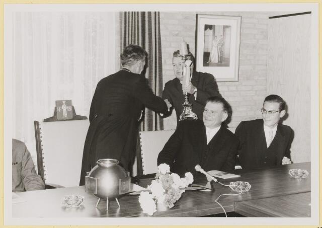 072947 - Opening gemeentehuis door de Commissaris van de Koningin Kortmann.  Bijzondere raadsvergadering. A. Wouterse overhandigt, na zijn toespraak, het geschenk aan de burgemeester.