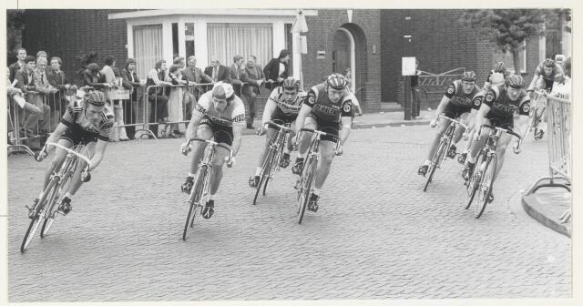 90938 - Made en Drimmelen. De Ronde van Made(1978).  De renners (profs) in de bocht van de Kerkstraat naar de Marktstraat. Op de achtergrond het huis van Willem van den Noort. Van het publiek is tweede van rechts Wout van Strien uit Made. Winnaar werd Aad van den Heuvel uit Dirksland; hij reed voor de TI-Raleigh ploeg.