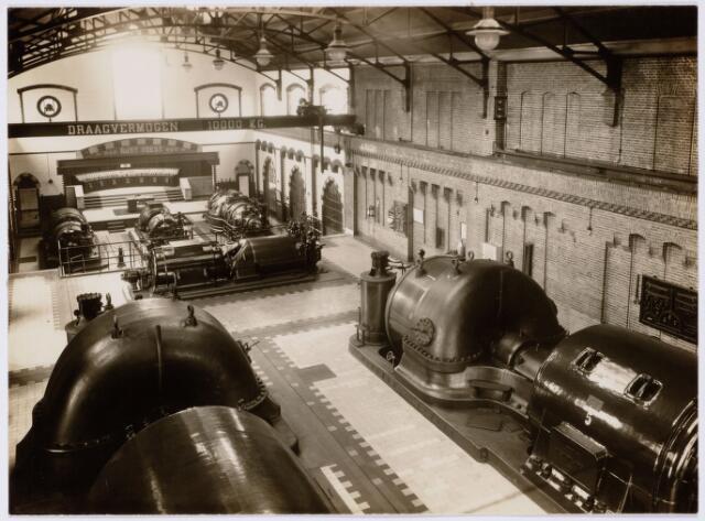 104159 - Energievoorziening. Gas- en Electriciteitsbedrijf (GEB). De bouwwerken voor de electriciteitsfabriek naast de gasfabriek zijn in volle gang en daarmee ontstaat het GEB , het gas- en electriciteitsbedrijf. Op 24 juni 1911 kan de levering van electriciteit plaatsvinden. In september 1954 wordt de electriciteitsproductie overgedragen  aan de PNEM; na 1958 is de centrale in Tilburg ontmanteld en gesloopt; Bij de komst van het aardgas verdwijnt ook het gasbedrijf.  De machinekamer in het gasfabriek;