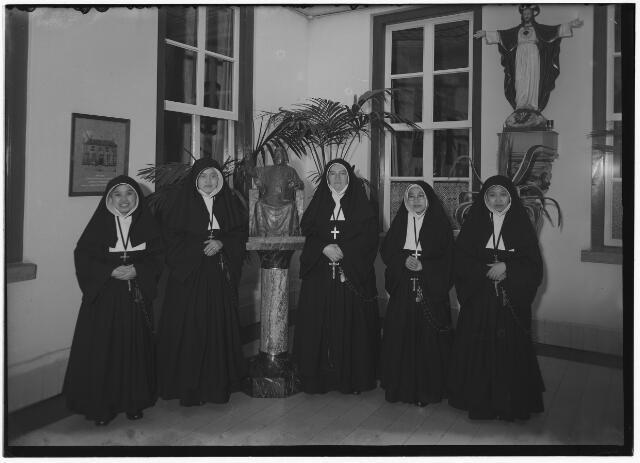 050955 - Foto genomen in het moederhuis van de zusters van liefde van O.L.V. Moeder van Barmhartigheid aan de Oude Dijk ter gelegenheid van het vertrek van enkele Indonesische zusters naar de missie in Padang. Van links naar rechts de zusters Bernardette en Antonia, moeder Magdalena van den Eijnde en de zusters Miriam en Johanna. In het midden het beeld van mgr. Zwijsen, de stichter van de congregatie.