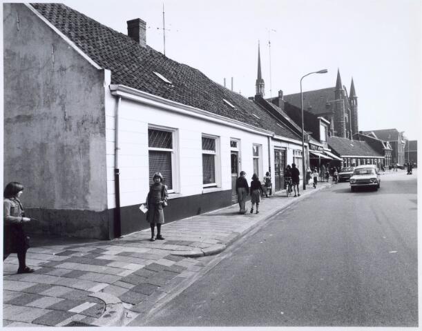 020430 - Hasseltstraat gezien in de richting van het Wilhelminapark medio 1976. Naast het winkelpand met de luifels, op de hoek met de Van Hogendorpstraat, gerestaureerde wevershuisjes. Daarnaast de kerk van Onze Lieve Vrouw van de H. Rozenkrans