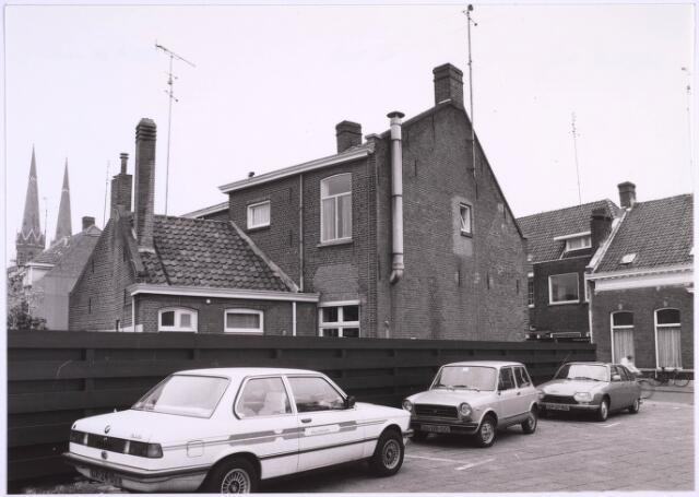 023292 - Parkeerplaats naast het pand St. Josephstraat 128 eind 1981. Links de torens van de Heuvelse kerk