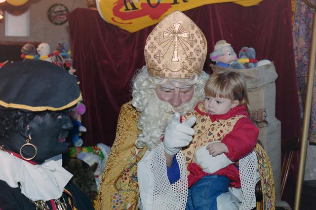 1237_001_003_009 - Feest. Korvel Winkelstraat. Sint Nicolaasviering. Een meisje zit op schoot bij Sinterklaas tijdens een Sinterklaasfeest georganiseerd door winkeliersvereniging Korvel Vooruit op 27 november 1999. Links staat Zwarte Piet, nog zwart geschminkt met gouden oorringen.