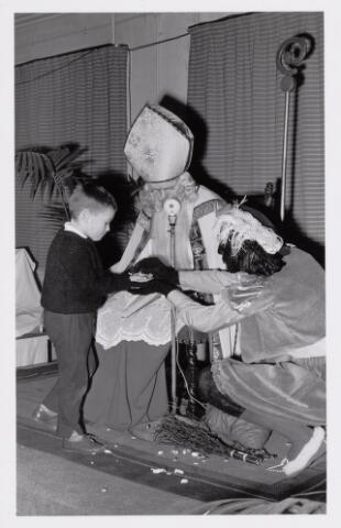 038703 - Volt. Oosterhout. Sint Nicolaasviering voor de kinderen van het personeel in 1960. Een handvol snoep. Fabricage- of productie vond in Oosterhout plaats van april 1951 t/m 1967. Sinterklaas. St. Nicolaas