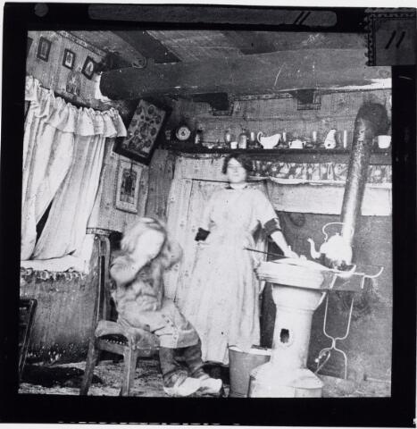 027392 - Krotwoningen. Oerlesestraat. Interieur. Deze woningen werden in 1913 door stedenbouwkundige Rückert als bouwvallig gekenmerkt. Kort daarna zijn ze gesloopt. Moeder met kind bij kachel.