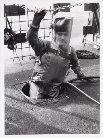 042244 - Riolering. Personeel van Van Hees bezig met het zuiveren en herstellen van de riolering in de Groenstraat ter hoogte van kinderwagenfabriek Mutsaerts. Een medewerker daalt af in het riool