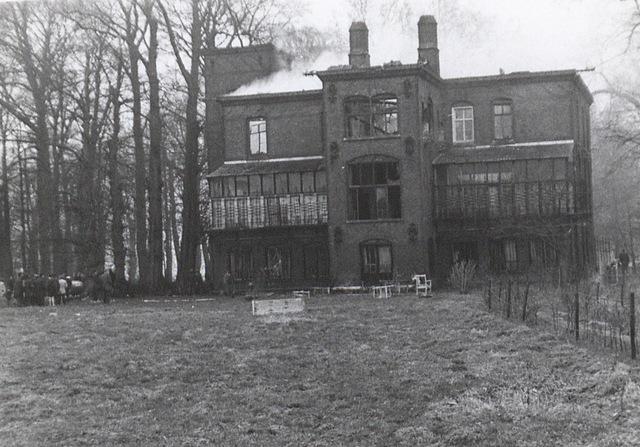 60110330 - Kasteel Nemerlaer tijdens een brand. Er komt rook vanaf het dak. Links heeft zich een groep toeschouwers verzameld. Waarschijnlijk is dit in 1969 waar door een zolderbrand het kasteel grotendeels uitbrandde.