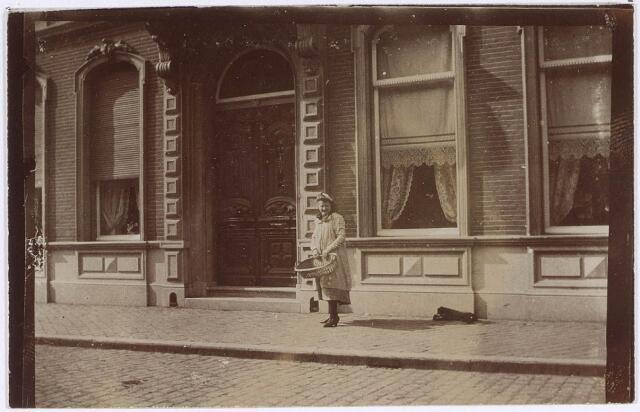021576 - Woonhuis van Bart Brands in de Heuvelstraat. Meisje met rieten mand poseert voor de voordeur. Thans staat hier het warenhuis van Vroom & Dreesmann