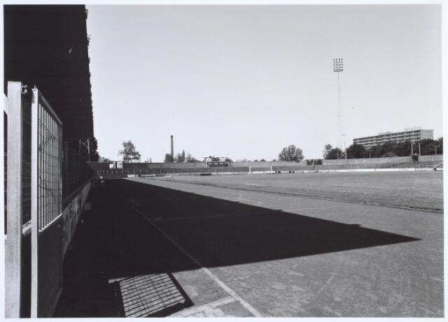019764 - Gemeentelijk sportpark aan de Goirleseweg, gezien in de richting van de Ringbaan-Zuid. De fabrieksschoorsteen is van textielfabriek H. van Puijenbroek. Het flatgebouw rechts staat aan de Generaal Smutslaan