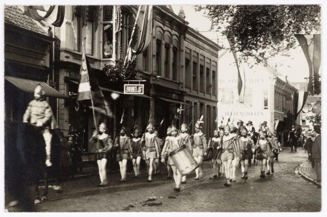 048918 - Optocht ter gelegenheid van de kroningsfeesten bij het 25-jarig jubileum van koningin Wilhelmina (1923-1924) deelnemers verzamelen zich op de Kromhout kazerne te Tilburg. Hier trekt de stoet door de Zomerstraat ter hoogte van de bekende lijstenmaker Briels