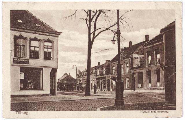 000741 - De noordelijke punt van de Heuvel bij de spoorwegovergang. Links de Spoorlaan. Het eerste gebouw rechts tegen de spoorwegovergang is café Kras, daarnaast café 't Centrum van Toon van der Loo. Geheel rechts het huis van dokter van Iersel, keel-, neus- en oorspecialist. Helemaal vooraan rechts een transformatorhuisje van het gemeentelijk electriciteitsbedrijf.