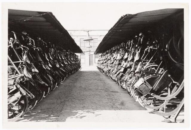 038646 -  Volt. Zuid. Gebouwen. Doorkijkje naar gebouw K van oost naar west. Achter de deur was de naaikamer annex wasserij gevestigd.   Zeker tot 1965 was hèt vervoermiddel om naar het werk te gaan de fiets. Omdat bij Volt toen 1000den mensen werkten, waren ook 1000den fiets-opbergplaatsen nodig. Elk personeelslid wat met de fiets kwam had z'n eigen genummerde fiets-opbergplaats. Voltstraat heette toen Nieuwe Goirleseweg.