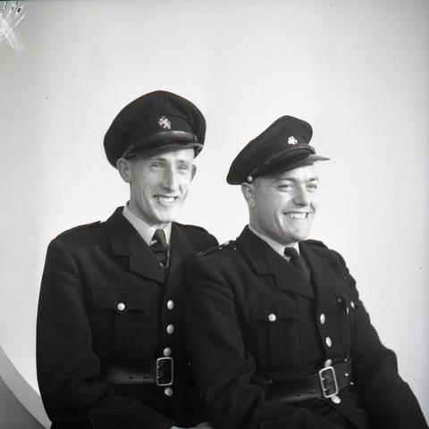 654732 - Portret van twee lachende agenten. ( links op de foto agent Pessers)