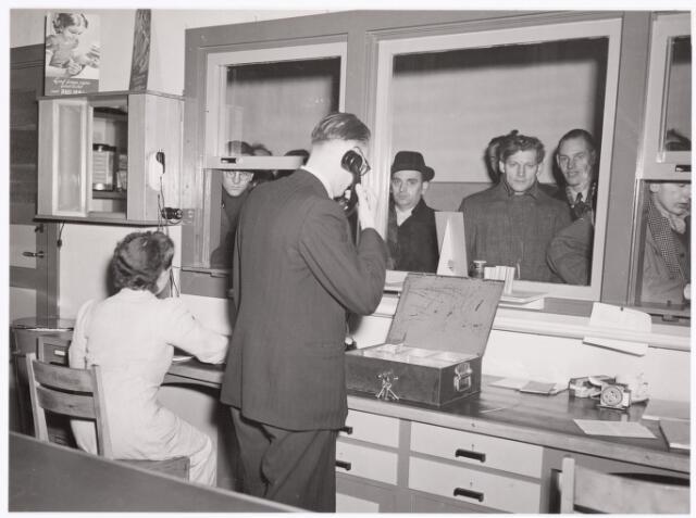 039332 - Volt, Hulp-afdelingen,  De personeelswinkel gevestigd naast de bovenkantine in gebouw B op complex Zuid. De winkel werd gerund door de heer Lanslots (met telefoon).  A.C.Lanslots heeft vanaf 1929 tot aan zijn overlijden 1961 bij de Volt gewerkt. Eerst als boekhouder en daarna in de personeelswinkel. De foto is genomen omstreeks 1955.