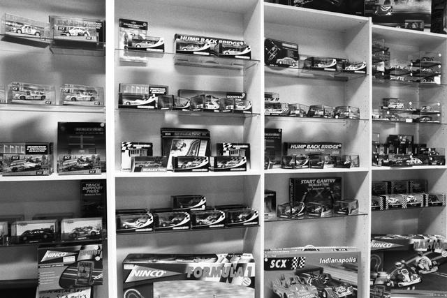 1237_002_196_019 - Middenstand. Ondernemer. Auto Brouwer in Tilburg op 23 december 2000. Overzicht van een stelling met miniatuur auto's en racebaan onderdelen.