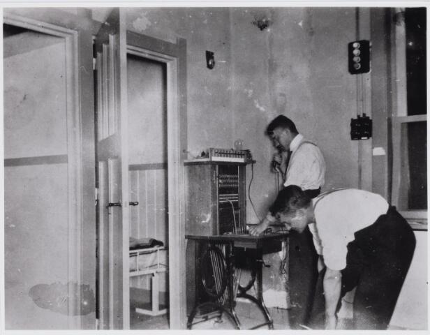 103598 - Brandweer. Seinkamer branndweerkazerne Capucijnenstraat (1933). Brandweerman Th. de Natris (op de voorgrond) trekt zijn laarzen aan (foto is in spiegelbeeld afgedrukt) Aan de telefoon B. Donders.
