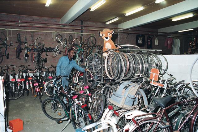 1237_010_756_018 - Winkels. Kringloop. Fietsen. Een man in overall is aan het werk tussen de fietsen bij kringloopbedrijf La Poubelle aan de Hoevenseweg.
