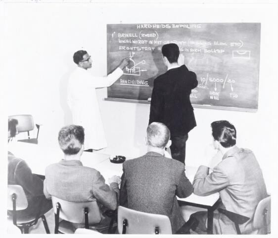 038578 - Volt. Noord. Opleidingen. Foto gebruikt voor tentoonstelling 25 jaar Volt vakliedenopleiding in september 1964. Theorieles voor aankomende vaklieden, in dit geval hardheidsmetingen van  metaal. Docent: Dhr. J. van Beers.