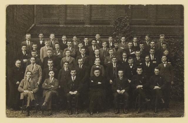 077228 - Pastoor ? met grote groep mannen, vermoedelijk aan de zijkant van de Johanneskerk.