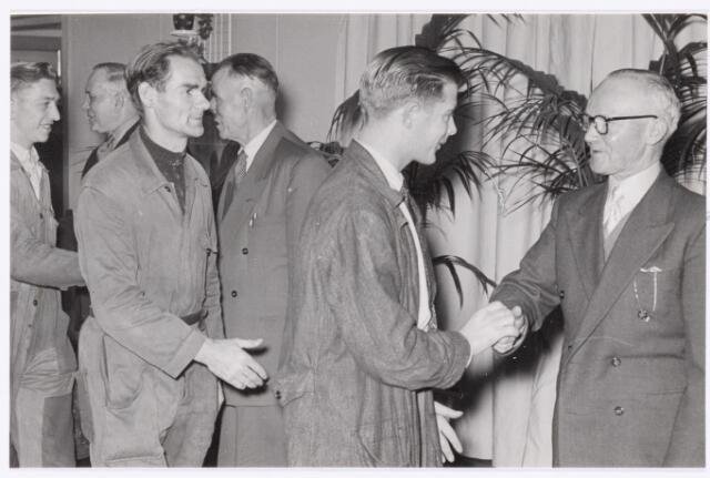 039076 - Volt. Afscheid. Met pensioen op 1-1-1956. Van rechts naar links: Vervoord, portier, de nestor van de afdeling bewaking, gefeliciteerd door Adrie Swinkels. Daarachter staat Lahay welke eveneens met pensioen ging.