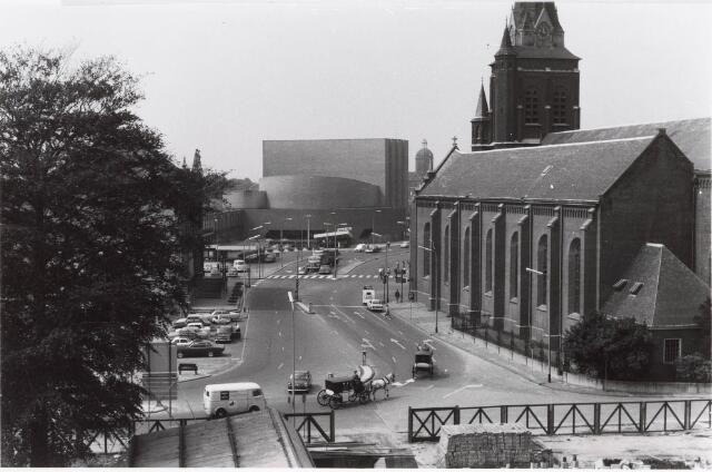 032572 - Verkeerssituatie met o.a. twee koetsen.  Bouw parkeergarage aan het Stadhuisplein. Op de achtergrond  de schouwburg, rechts de Heikese kerk en links is nog net de voorgevel van het oude stadhuis zichtbaar.