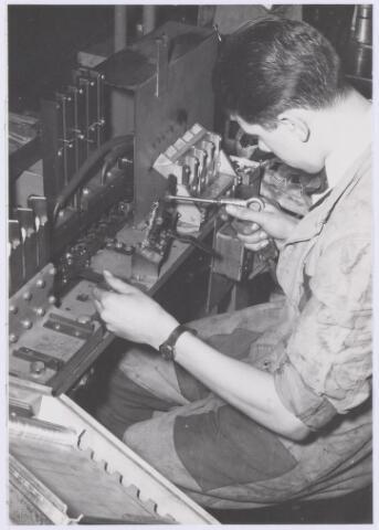 038989 - Volt Zuid. Fabricage. Productie. Condensatoren. Een vorm van automatisering in de afd. lucht-condensatoren bij Volt rond 1955. Een condensatorpakketje bestond soms wel uit 50 of 60 plaatjes. Die moesten toen nog handmatig gestapeld worden. Door de toepassing van vacuüm kon in een keer het 4 voudige gedaan worden in dezelfde tijd. Met het vacuümpistool werden de plaatjes uit de vul magazijntjes genomen en op het te stapelen condensatorpakket gelegd.