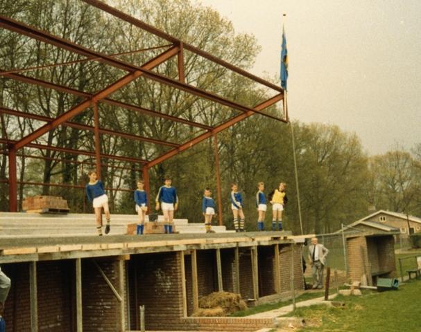 800077 - Voetbal. Bouw van de tribune van voetbalvereniging Taxandria in Oisterwijk. Het hoogste punt is bereikt. De vlag wordt gehesen en jonge spelers staan op de tribune in aanbouw.
