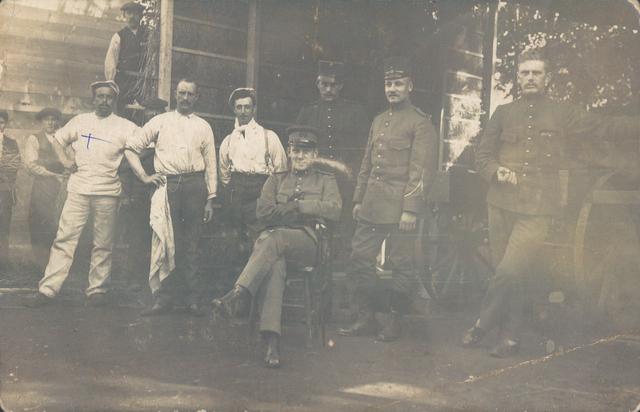 651755 - Mobilisatie 1914-1918. Militairen / douaniers (rechts) worden op deze foto vergezeld door leken - waarschijnlijk plaatselijke bewoners in dienst van de douane. De man die zit is waarschijnlijk een sergeant - zijn pet is duidelijk anders dan die van de anderen én hij zit op de enige aanwezige stoel. Alleen de man die recht van hem staat heeft puttees aan met bottines, de anderen dragen allemaal gewone lage schoenen en sokken. De mensen in niet militaire kleding dragen een soort sloffen. Waar ze zich bevinden is niet heel duidelijk. Het lijkt een stal te zijn met recht hooi of stro hoog opgetast; de slaapplaats van de 'mannen'.