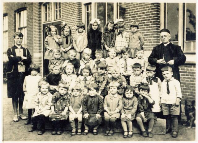 062054 - Basisonderwijs. Klassenfoto. Bewaarschool in Enschot aan het Torenpad rond 1930; op de 1e rij v.l.n.r.Mien Denissen, Sjaantje Vugts, N.N., Jo van Zeeland, Mia Vugts, Annie  Bult en Pietje Mol. Op de volgende rij v.l.n.r. Fien van Baast, Riet Denissen, Corrie v.d. Wiel, Anneke de Jong, N.N., Cor van Turnhout, Harry van Baast , Trees Segers en Jo Schoonings. Volgende rij v.l.n.r. Gerard Bertens?, Jo Schellekens, van Os, Piet Schoonings, Harry Smetsers, Wout van de Wouw en Martien van Zeeland. Op de laatste rij v.l.n.r. Riet van Esch, Anneke van de Wouw, Stien de Bakker, Fien de Jong, Cato de Kroon, Jeanne Vugts en Frieda Verhoeven. Links Juffrouw Marie Denissen en rechts pastoor Schellekens