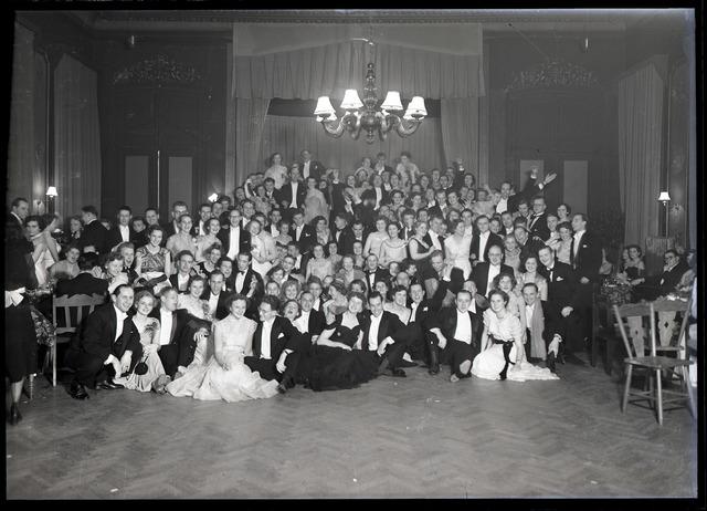 - Groepsfoto van jonge mannen en hun dames in galakleding. Feestavond.