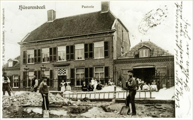 054511 - Koestraat met op de achtergrond de voormalige pastorie gebouwd in 1834 door pastoor Van Asten. Rond 1950 betrok de pastoor een nieuwe pastorie en ging het gebouw dienst doen als jeugdherberg.
