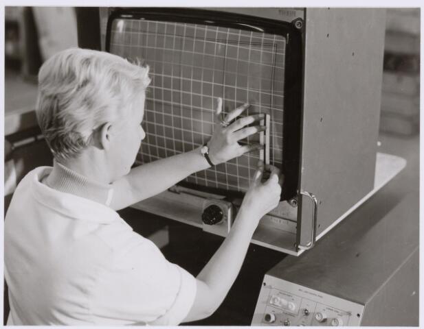 038978 - Volt.Noord.Productie of fabricage afd. Deflectie Units. Monitor meten (kwaliteit bepalen) van deflectie units rond 1975. Hier wordt de afwijking gemeten tussen de kleuren rood, groen en blauw. Om de kwaliteitsbewaking en processturing mogelijk te maken moesten 150 metingen worden verricht per deflectie unit. Een zeer tijdrovende bezigheid. Rond 1975 nam de automatisering van dit proces een aanvang. In 1985 was het mogelijk met 25 volautomatische meetpunten de vereiste 6 metingen per meetpunt (is 150 metingen) in een keer in enkele seconden te doen. De uitslag was dan af te lezen op een computerscherm. De computer berekende ook gemiddelde en spreiding van de productie. Dit was a.h.w. een on-line kwaliteitsbewaking.
