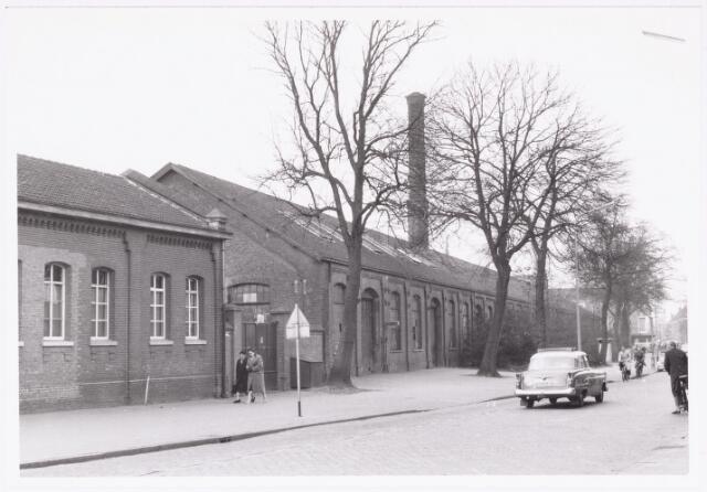 037066 - Spoorwegen, Centrale Werkplaats, Atelier, NS.: De voormalige loods van de Centrale Werkplaats in 1959 aan de Koestraat. Op de achtergrond de kledingzaak van de Cock.