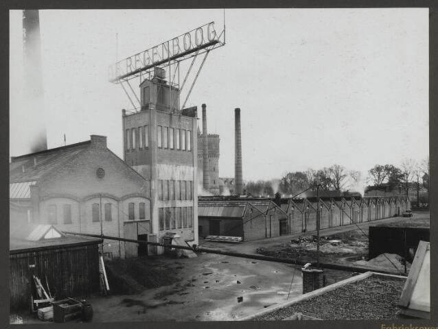 071835 - Overzicht vanaf de westijde van het fabriekscomplex van de stoomververij en chemische wasserij De Regenboog aan de Bredaseweg te Tilburg. In het midden de watertoren van de fabriek, daarachter de Tilbursge watertoren aan de Bredaseweg. De foto is afkomstig uit een album dat werd gemaakt ter gelegenheid van het 40-jarig jubileum van textielfabriek De Regenboog op 2 december 1930.