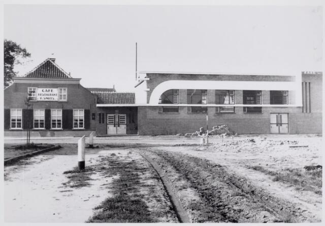 046594 - Hoek Tilburgseweg-Van Haestrechtstraat. Op de achtergrond café Harrie Smits op de hoek Tilburgseweg-Dorpsstraat. Achter dit café werd in 1924 een houten loods gebouwd die als concertzaal zou dienen voor harmonie Oefening en Uitspanning. Op 29 juni 1933 werd de nieuwe harmoniezaal achter het pand van Smits geopend. Na de oorlog begon Harrie Smits in deze zaal, in samenwerking met Biemans, een bioscoop, die bekend werd als het 'Alpha theater'. De eerste en laatste bioscoop van Goirle werd na ruim tien jaar gesloten wegens gebrek aan belangstelling.