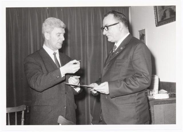 039461 - Volt, Zuid. Hulpafdelingen, Brandweer. De heer Jo Vermeulen bij het overhandigen van het Zilveren kruis voor 25 jaar trouwe dienst bij de bedrijfsbrandweer van Volt in 1965. De onderscheiding werd bij de heer van Zuijlen wegens ziekte thuis uitgereikt.