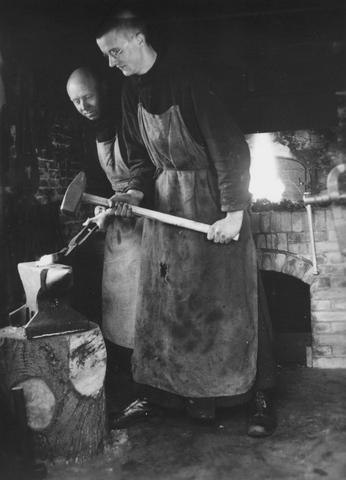 105235 - Monnikenleven De smederij van de Sint Paulusabdij rond 1938, met de broeders Meeus en Van der Biesen aan het werk op het aambeeld.  Kloosters