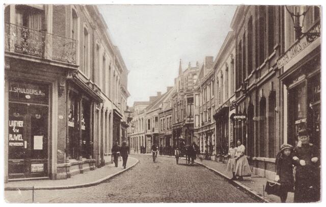 001651 - Nieuwlandstraat in zuidelijke richting. Links op de hoek van de Mariastraat het pand M. 1183, later Nieuwlandstraat 16.  Rond 1900 zat in dit pand de kruidenierswinkel 'Au Bon Marché' van de familie Blous. Na het vertrek van Cornelia Isabella Dols, weduwe van M.J. Blous met haar gezin naar Princenhage in 1912 kwam er de rijwielhandel van J.B. Smulders Azn. Deze zaak bleef bestaan tot midden jaren vijftig. Links bij het uithangbord 'apotheek' (M766, later huisnr. 19) de apothekerszaak van Jan Isidoor Keijzer. Hij was getrouwd met Constantia van Gils, dochter van apotheker Van Gils, de voorganger van Keijzer aan de Nieuwlandstraat. Links van dit pand de zaak van Antonius C. de Jong, huisschilder en handelaar in glas en verfwaren. Hij opende zijn 'handel in verfwaren en vernissen' aan de Nieuwlandstraat in juli 1894. Rechts van de apotheek, Nieuwlandstraat 17, de zaak in heren- dames en kinderschoenen van Woutherus Burmanje, schoenfabrikant, voorheen het schoenmagazijn van de weduwe Burmanje-Couwenberg. Na Burmanje zat in dit pand de bloemenzaak van de firma Vugts.
