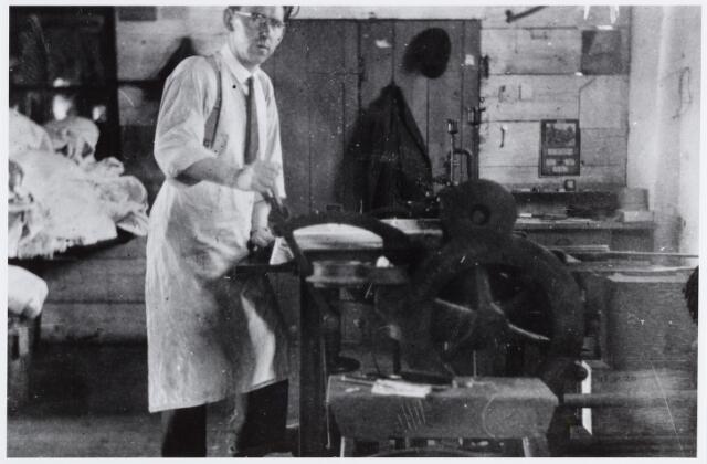 """057179 - Oisterwijk. Gerard Groenland bezig aan de """"boordenstrijkmachine"""" in de Eerste Oisterwijksche Stoomwasch- en Strijkinrichting Reingoed aan de Roode Brugstraat in de jaren dertig."""